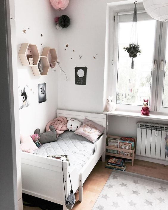 a cozy and soothing kid's room done in white, black and pink, with a white IKEA Sundvik bed, hex shelves, paper lanterns and a potted plant
