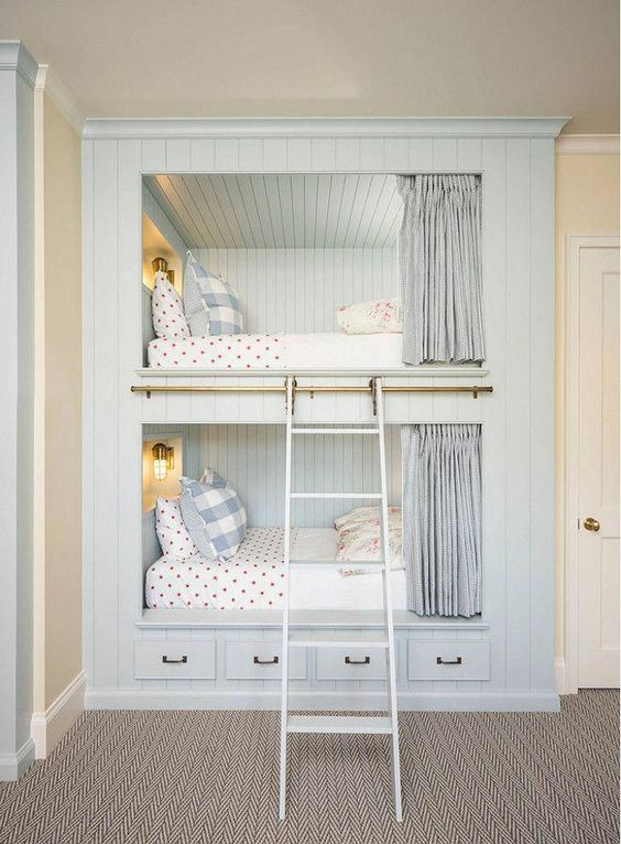 a cozy built-in bunk bed unit in pale blue, with wall lamps, a ladder, curtains and storage drawers in the lower part