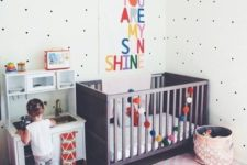 a cute pastel nursery with a dark stained Sundvik crib, colorful touches and an artwork, a play kitchen and polka dot walls