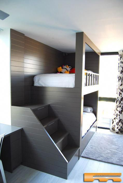 a dark stained ubnk bed unit with a staircase and wall lamps at the headboard of the bed