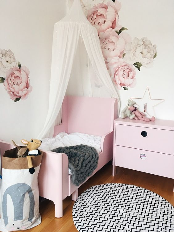 a delicate girl's bedroom with handpainted florals, a pink Sundvik bed, a printed rug, a canopy and a storage bag
