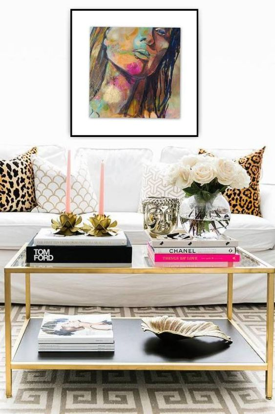 a glam black and gold coffee table with stacks of books, pink candles in floral candle holders, white blooms in a clear vase