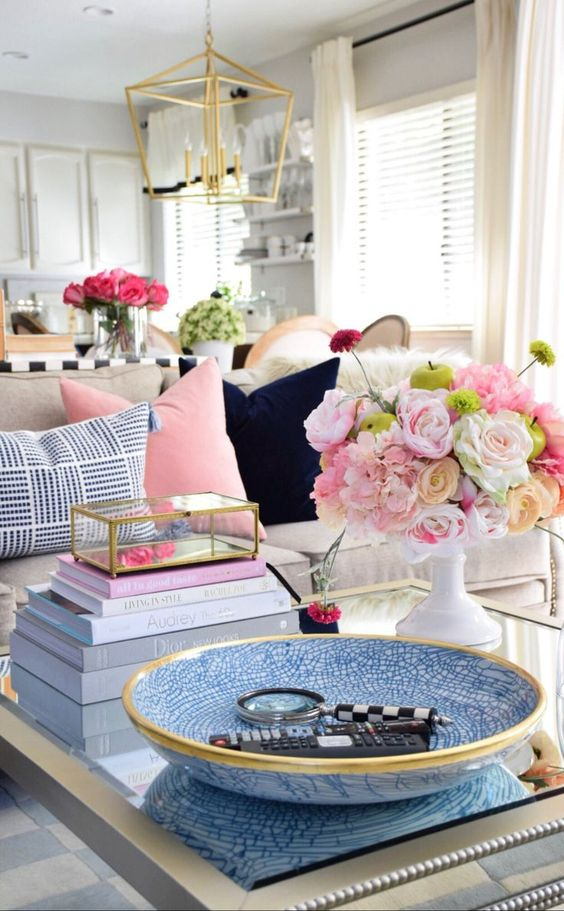 a glam gold and blue coffee table with a blue bowl, a stack of books, bright blooms in a white vase