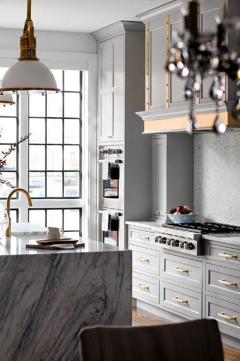 a glam grey kitchen with vintage cabinetry, gold handles and edging, a white marble kitchen island and brass fixtures