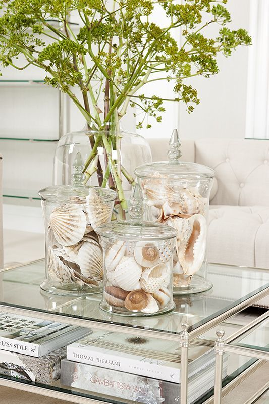 a glass coffee table with books, large jars with seashells and an oversized vase with some greenery