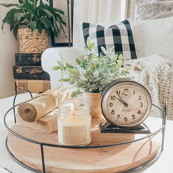 a glass tray with a large candle in a mason jar, a vintage clock, potted greenery and some old books
