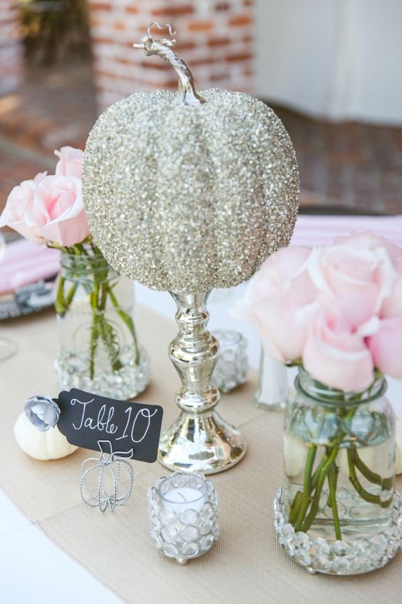 a gold glitter pumpkin on a mercury glass stand is a bright and fun centerpiece for the fall