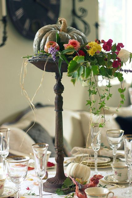 a heirloom pumpkin with faux apples and bright cascading blooms and greenery ona dark wooden stand is a lovely centerpiece