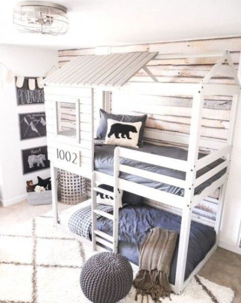 a house shaped bunk bed unit for two, built in lights and a ladder to reach the upper bed