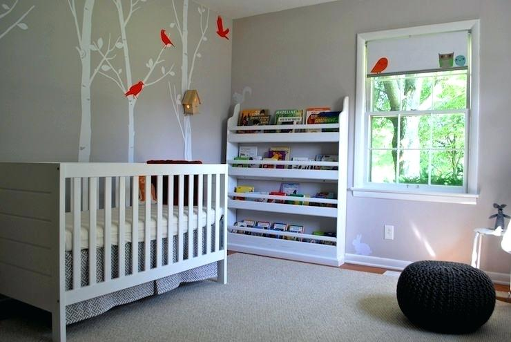 a laconic nursery with painted trees on the wall, a bookshelf, a Sundvik crib and a black crochet pouf