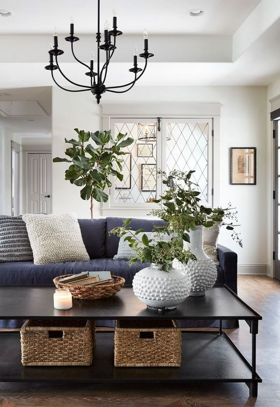 a large black coffee table with basket boxes, white vases with greenery, a woven catch-all and a candle
