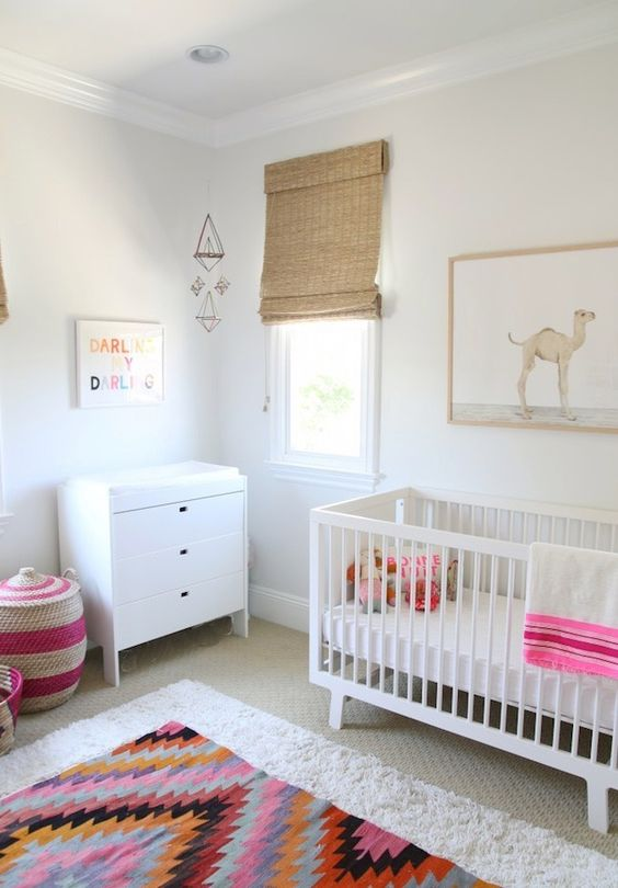 a light-filled nursery with white furniture including an IKEA Sundvik crib, a colorful rug, basket and bedding and wicker shades