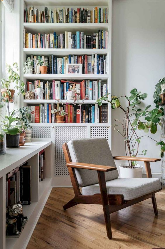 a lovely home library nook with a large bookcase and a large shelf by the window plus a chair