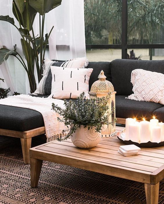 a low wooden coffee table with an arrangement of pillar candles in a tray, potted greenery and a candle lantern