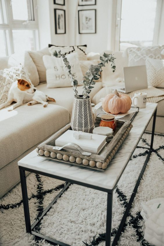 a marble coffee table, a wooden tray with beads, a vase with greenery, some candles and books and a pumpkin