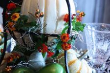 a metal tiered stand with hay, faux veggies and fruits and bright blooms plus large pumpkins for fall decor