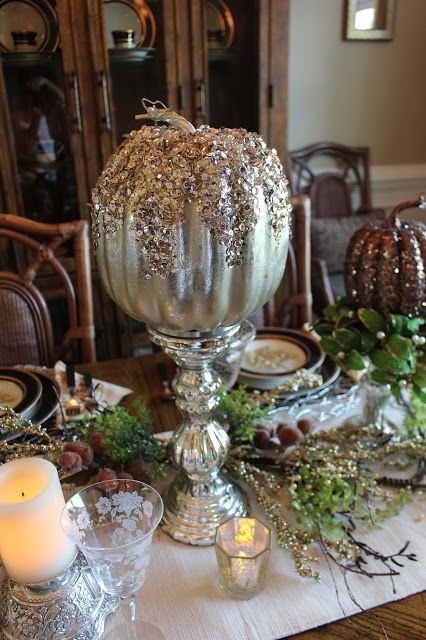 a metallic pumpkin with sequins and glitter on top on a vintage mercury glass stand as a glam centerpiece