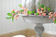 a milky painted pumpkin on a matching wooden stand, with berries looks and feels very farmhouse-like