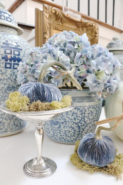 a mini blue velvet pumpkin with moss placed on a chic vintage stand brings elegance and chic to the space