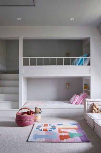 a minimalist room with bunk beds, a ladder and small wall lamps and shelves for storage