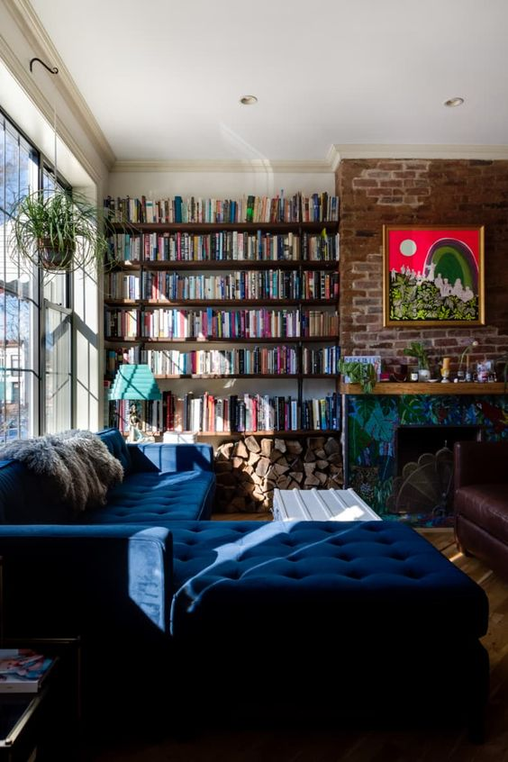 a modern and bold home library with dark floating shelves, a navy L shaped sofa and a bold artwork