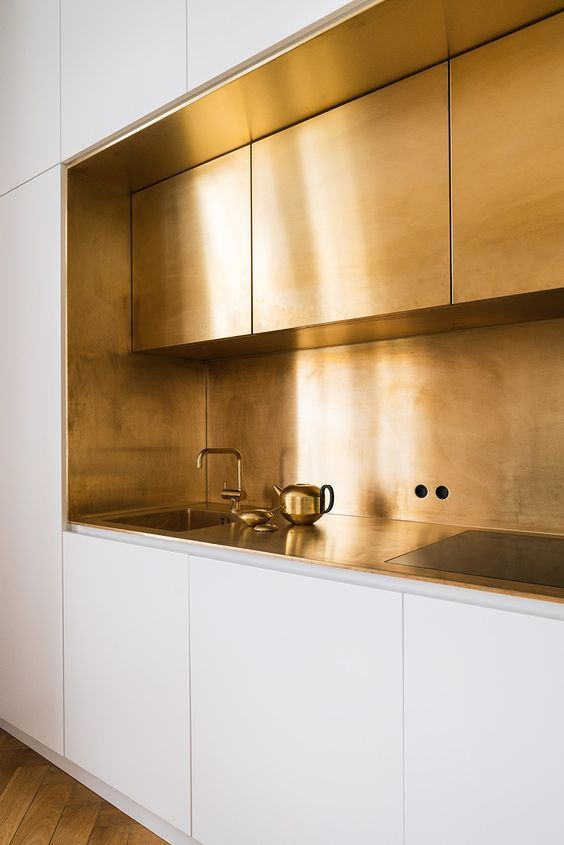 a modern glam kitchen with white and brass cabinets, a brass backsplash and countertops plus fixtures for a wow look