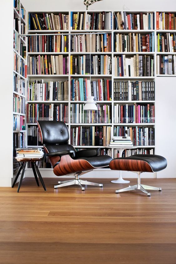 a modern home library nook with an oversized L shaped bookcase, a black leather chair with a footrest