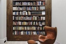 a modern home library with a bookcase in a wide wooden frame, with a comfy leather chair and a red pendant lamp