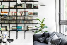 a modern home library with a floating black bookshelf unit and some contemporary furniture