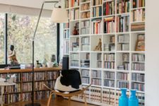 a modern home library with a large bookcase and a built-in window unit plus a cowhide chair