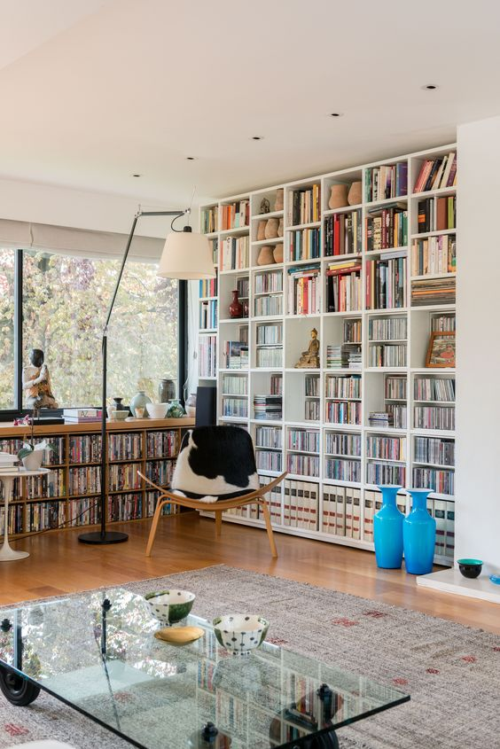 a modern home library with a large bookcase and a built in window unit plus a cowhide chair
