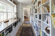 a modern home library with a large shelving unit that doubles as a space divider and a shelving windowsill unit