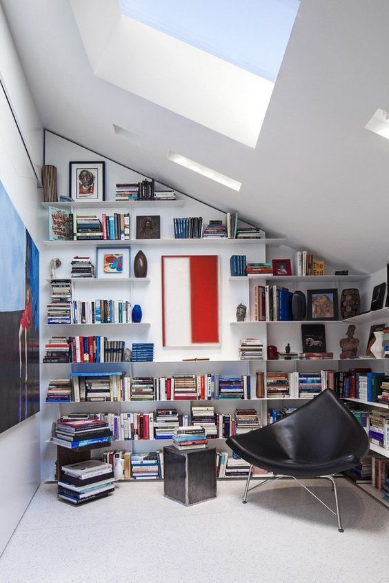 a modern home library with a skylight, some floating bookshelves and a black leather chair