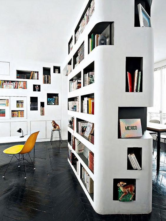 a modern home library with a white and black bookcase with niches that doubles as a space divider