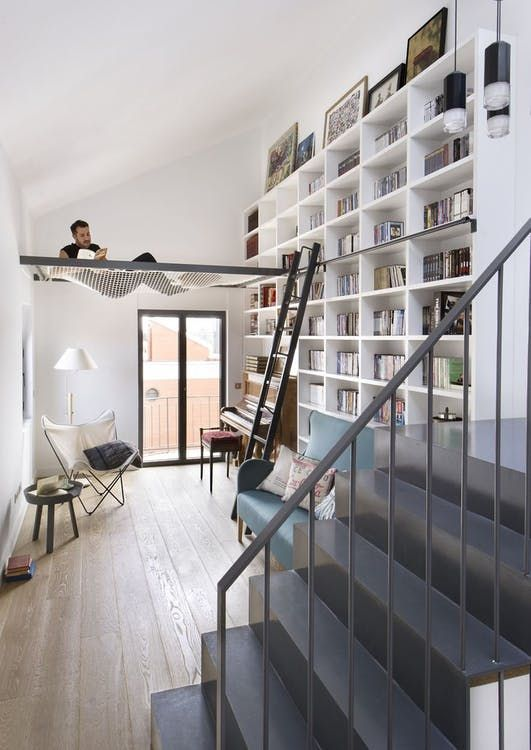 a modern home library with a white bookshelf unit, stairs, comfy chairs and a net for relaxing there