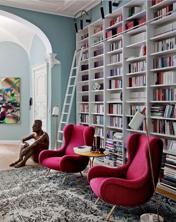 a modern home library with an oversized white bookcase with steps and two chic chairs in red for a cozy nook