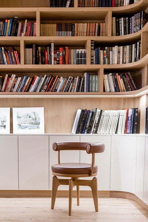 a modern home library with built in and lit up shelves and a single whimsy leather chair in front of them