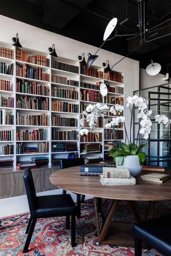 a modern home library with built in bookshelves in white and a large round table and black leather chairs