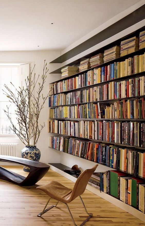 a modern refined home library with an oversized floating bookshelf unit, a dark wooden table and a leather chair