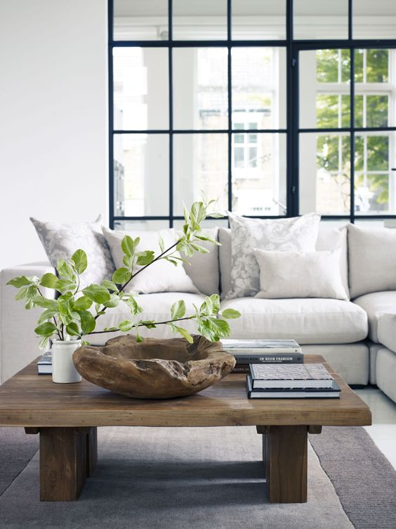 a modern rustic coffee table with a rough wooden bowl, books and a greenery arrangement in a vase
