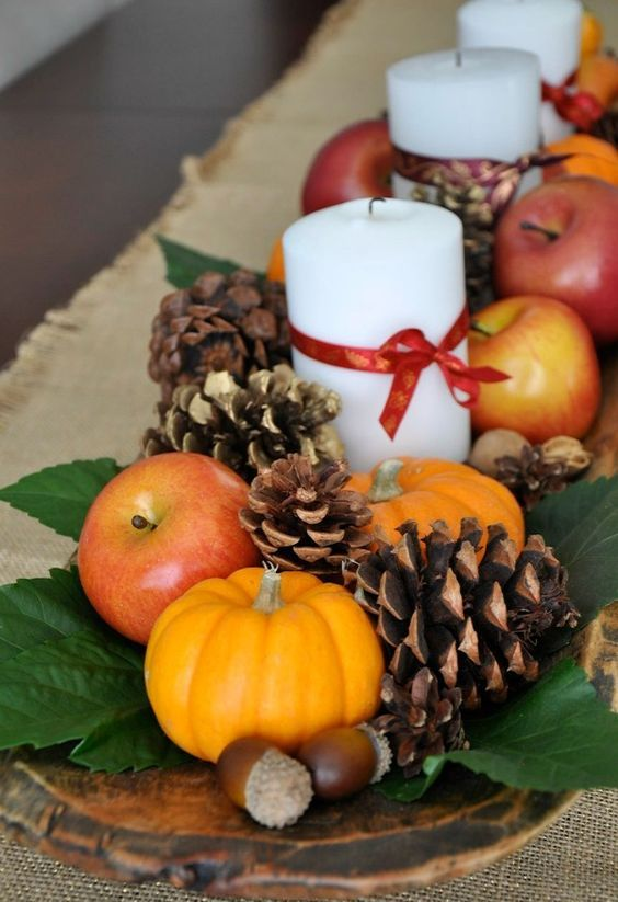a natural fall centerpiece of a dough bowl, foliage, pinecones, nuts, acorns, apples, pumpkins and candles