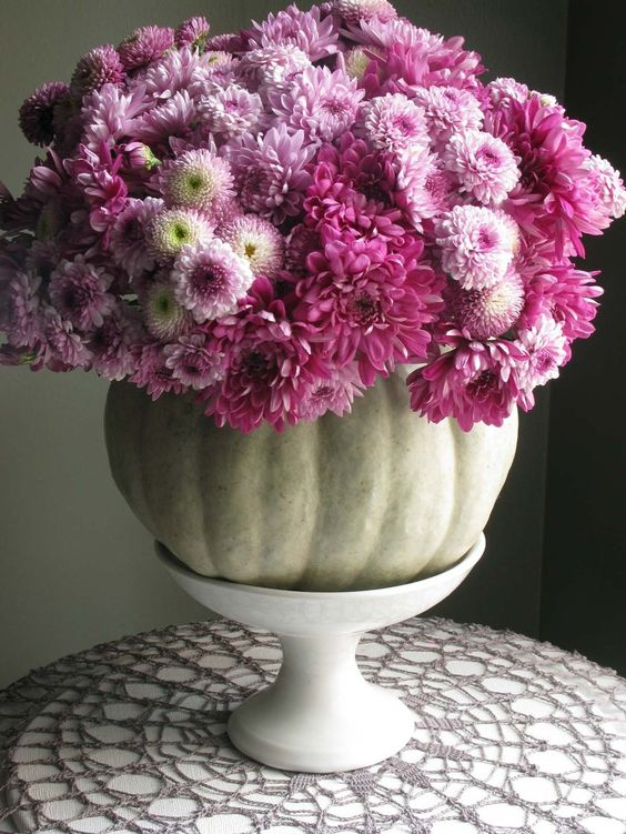 a natural pumpkin with lots of purple blooms on a white stand is a chic and bright rustic centerpiece