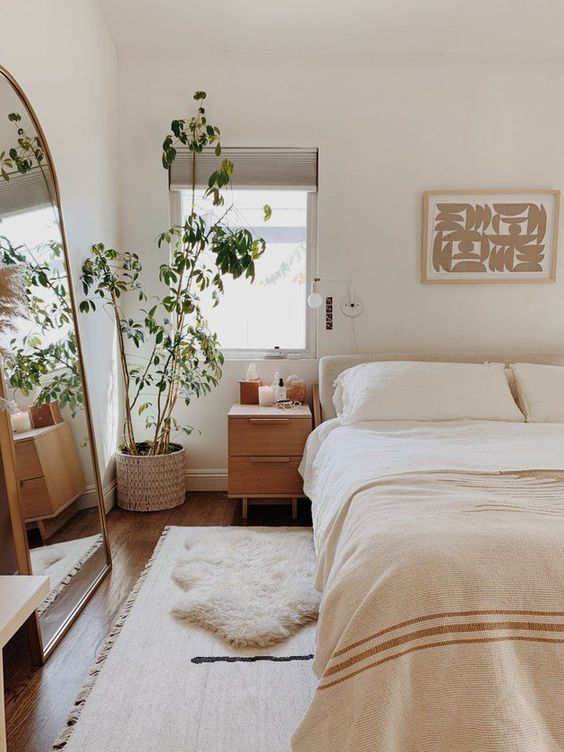 a neutral color scheme plus a large floor mirror make the bedroom look big and very welcoming