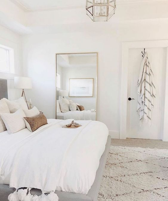 a neutral farmhouse bedroom looks bigger thanks to the neutral color scheme and thanks to a large mirror