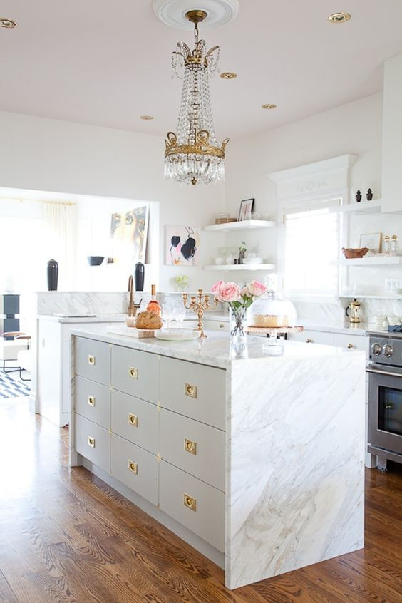 a neutral glam kitchen with white cabinets, white marble countertops and a backsplash, gold handles, a crystal chandelier
