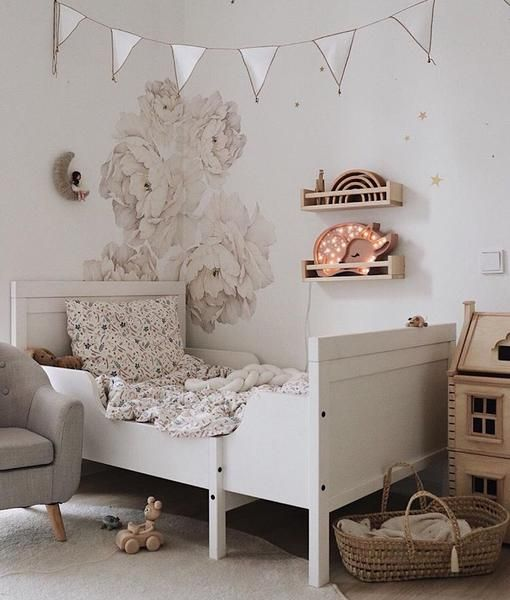 a neutral romantic kid's room with handpainted florals, a white Sundvik bed, a banner, a playhouse and baskets