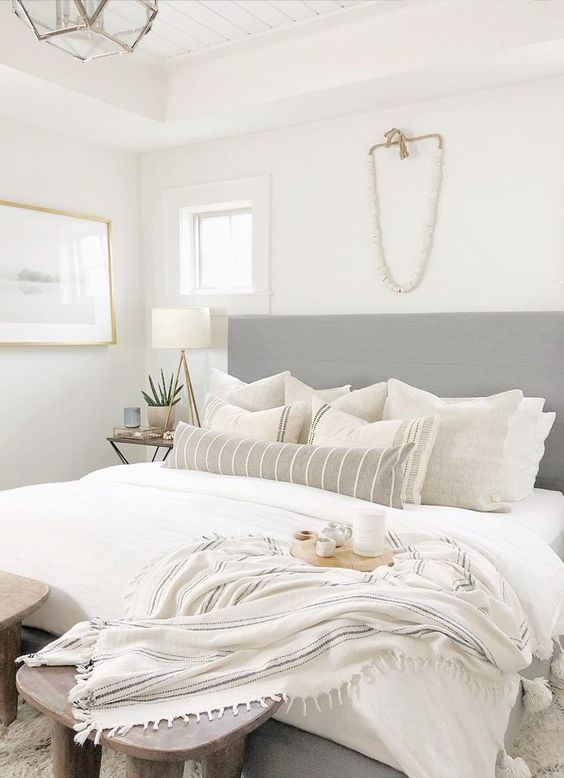 a neutral small bedroom looks larger cause of an extended headboard, a neutral color scheme and enough light