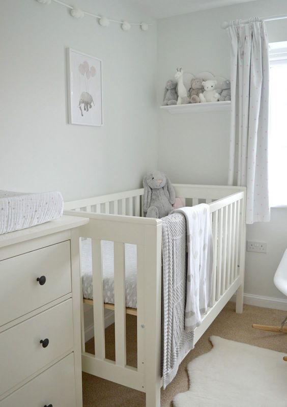 a neutral soothing nursery done in dove grey and off whites, with an IKEA Sundvik crib and cozy and cute toys