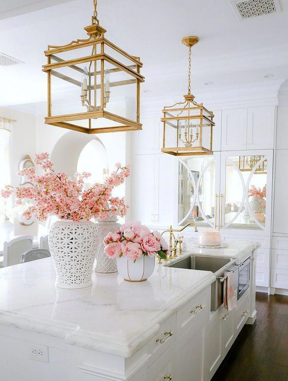 a neutral vintage glam kitchen with white cabinetry, touches of mirror, white marble countertops, gold handles and gold cage chandeliers