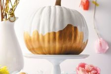 a pretty white and gold pumpkin on a stand is a cool centerpiece in modern style or just decoration